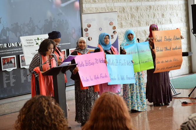 At the launch of the report Making Votes Count Where We Live, women hold up posters with four strategies to encourage people to vote, taken from the report.