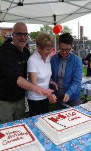 Councillors Jeff Leiper and Catherine McKenney, with Senator Nancy Green Raine (centre), cutting the birthday cakes. Photo: Carol Sissons.
